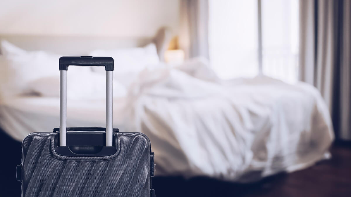 suitcase next to unmade bed