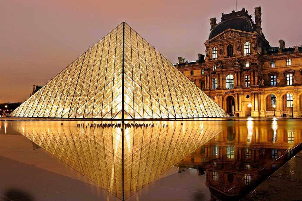 5 Best European Adventures for History Buffs. View of Louvre glass pyramid in Paris France