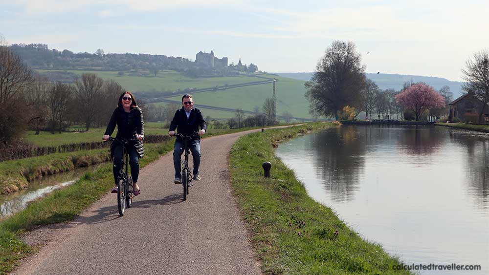 Couple bike riding along the towpath with Châteauneuf-en-Auxois in the distance