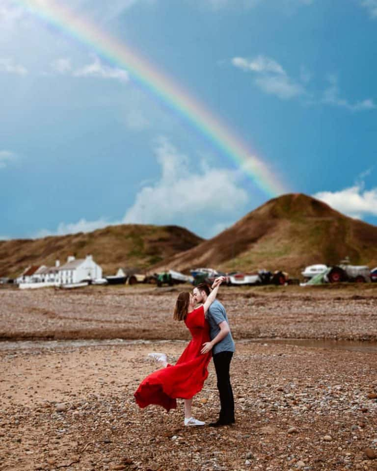 Smartphone travel photo of a couple kissing under a rainbow