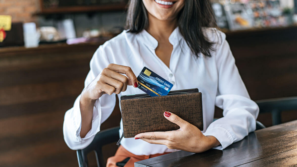 pulling out a travel rewards credit card from wallet