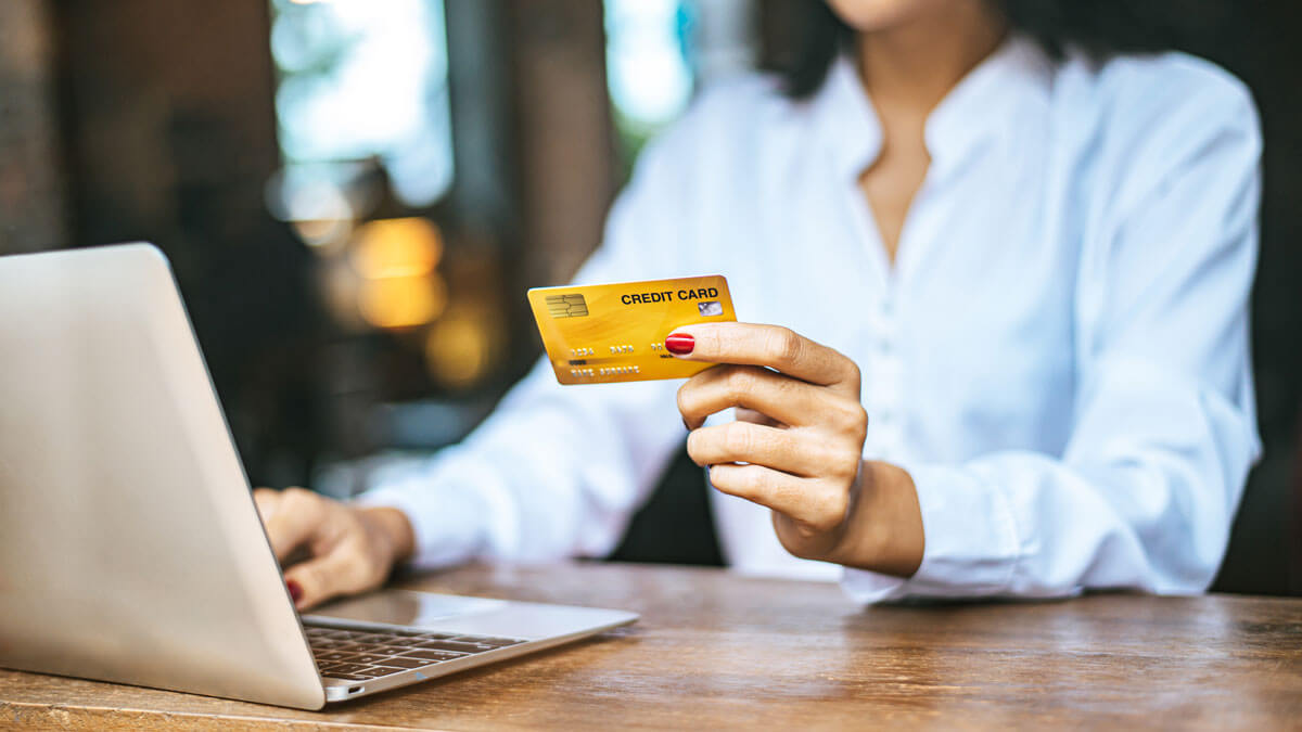 paying bills online on laptop with travel rewards credit card