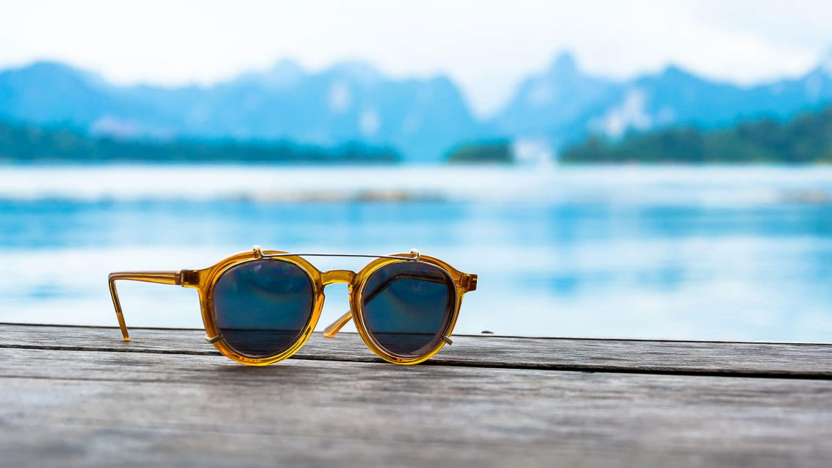 guide to pick perfect sunglasses - sunglasses on wood deck